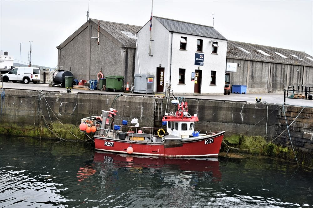 A fishing boat reflected in the water in the harbour at Stromness, Orkney