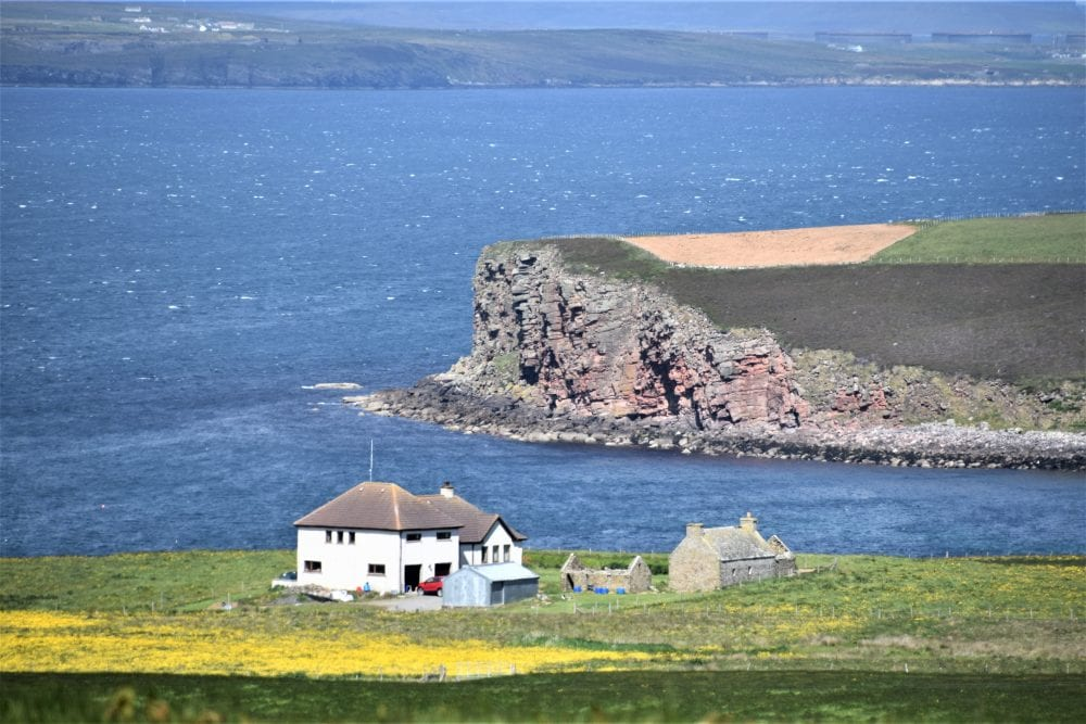 View of crumbling cliffs behind a farmhouse on the loch at South Ronaldsay, Orkney