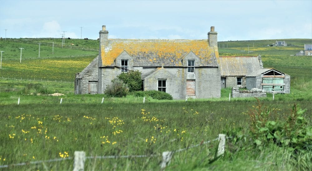A stone farmhouse with a lichen covered roof, Orkney