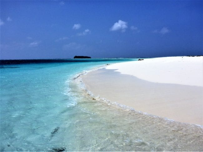 The white sand of Picnic Island dips into the sea in the Solomon Islands