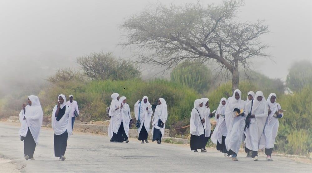 Schoolgirls in uniform wandering a long a misty road in Somaliland
