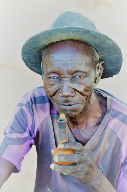 A portrait of an old man wearing a brimmed hat, pipe in hand