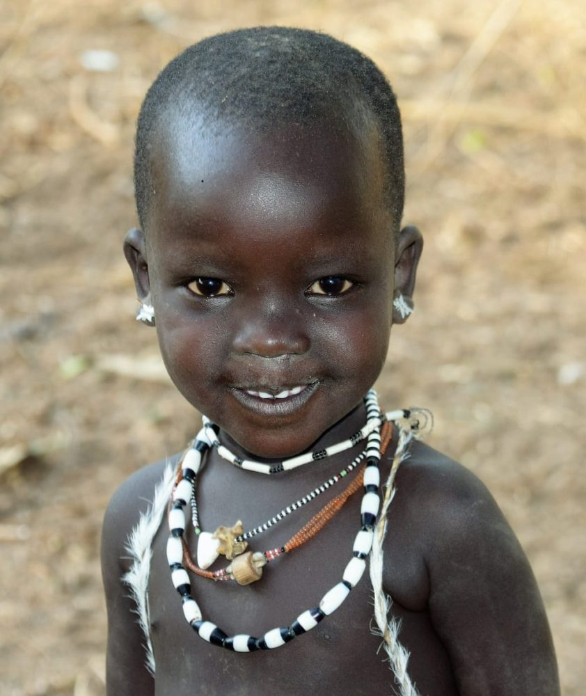 Portrait of a smiling girl wearing several bead necklaces