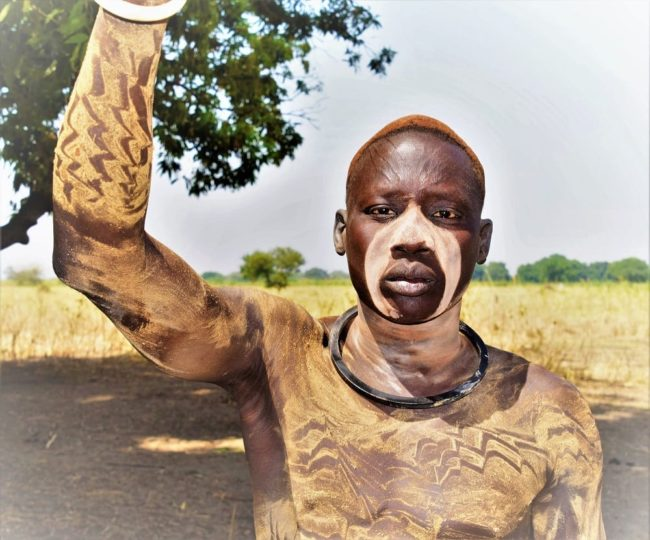 A headshot of a Mundari warrior with painted and scarified body, South Sudan