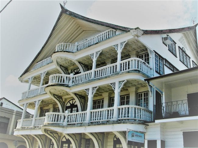 A white wooden colonial house with balcoines and pointed roof at Paramaribo Suriname