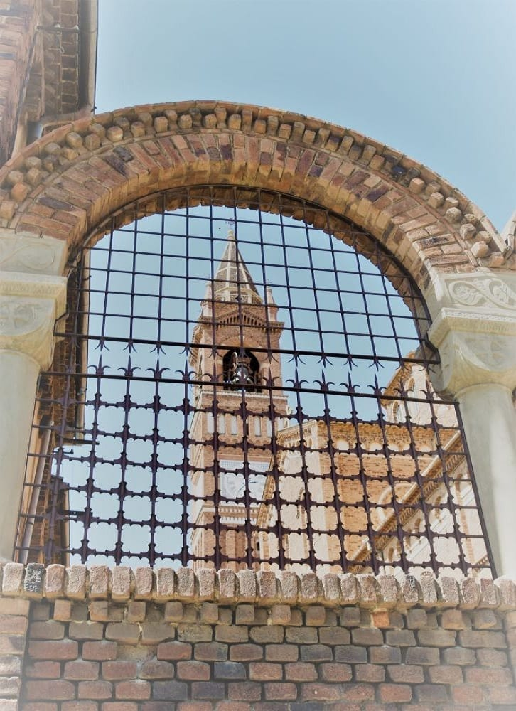 The cathedral bell tower seen through an arch with a grille