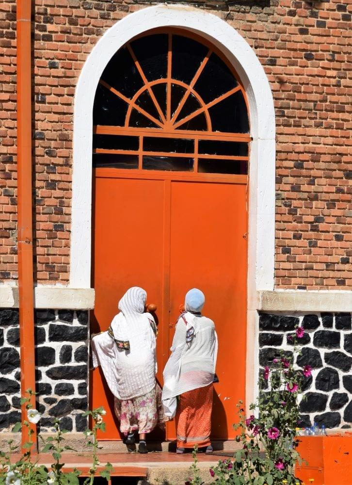 Tow women wait outside a huge orange door at a convent in Asmara