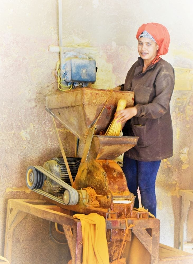 A lady grinds chillies on a machine in Asmara
