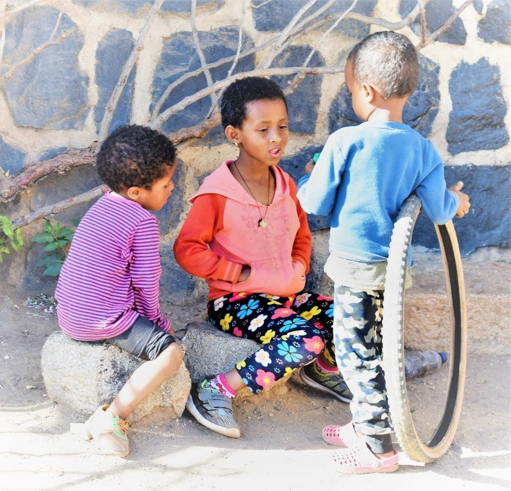 Three young boys playing with a bicycle tyre