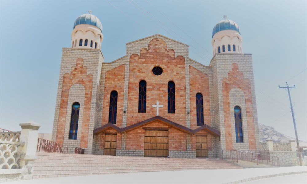 A red brick church with two blue domes on its towers in Eritrea