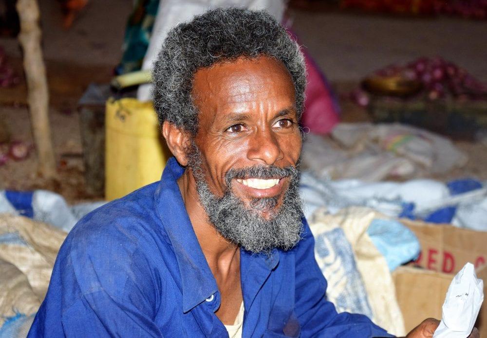 A portrait of a bearded market worker