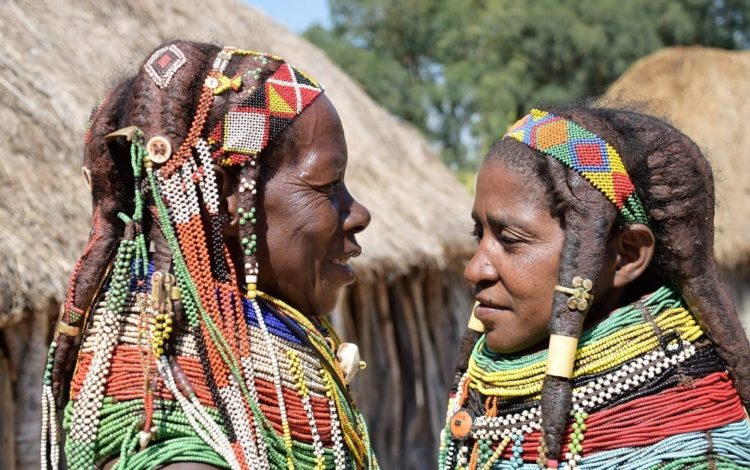 Headshot of two Muila women in profile facing each other