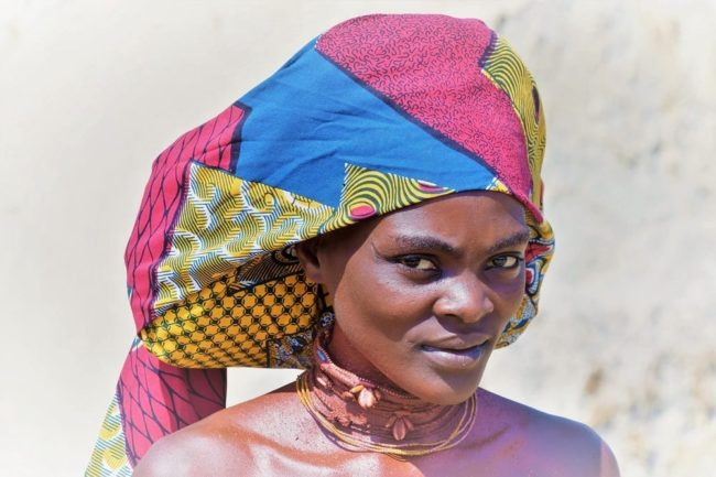 A headshot of a Mucabal woman with typical framed ompota headdress in Angola