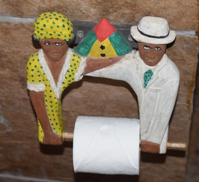 A wooden African lady and man hold the toilet roll in Sao Tome