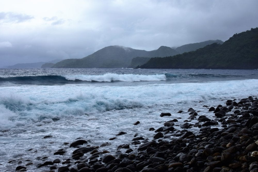 Breakers on a black volcanic rock beach in American Samoa