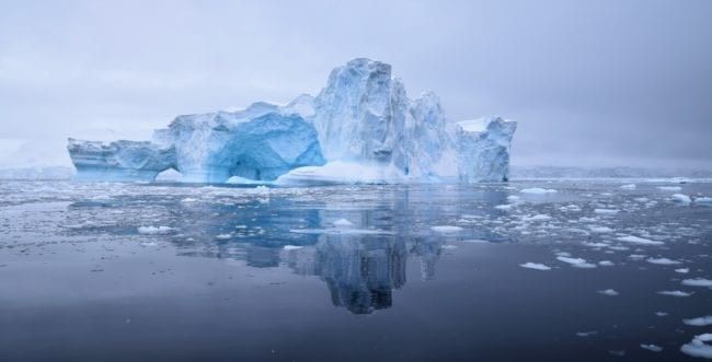 A beautiful blue iceberg is reflected in a steel grey sea in Antarctica