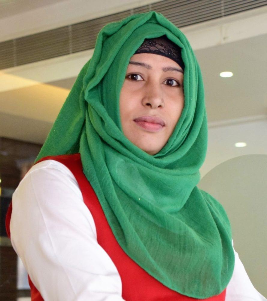 Portrait of a Bangladeshi lady wearing a bright emerald headscarf
