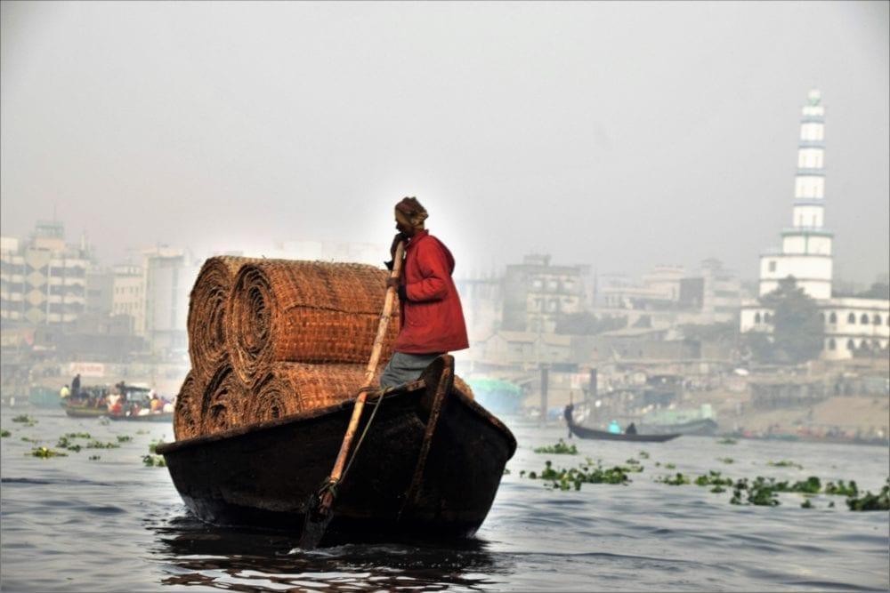 A tradesman poles a barge on the Buriganga River in Dhaka