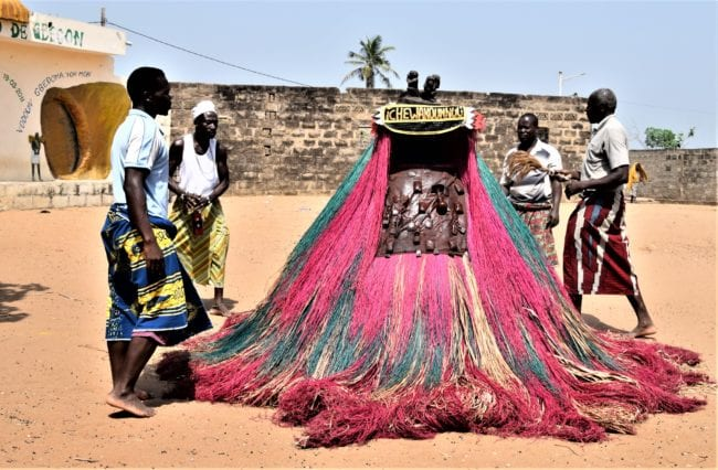 A New Year Voodoo dance ceremony, pink raffia skirted masks dance with seemingly no person inside