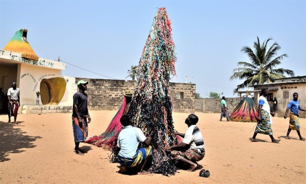 A New Year Voodoo dance ceremony, the tinsel like tower hidden beneath the 'dancers' skirts grows tall