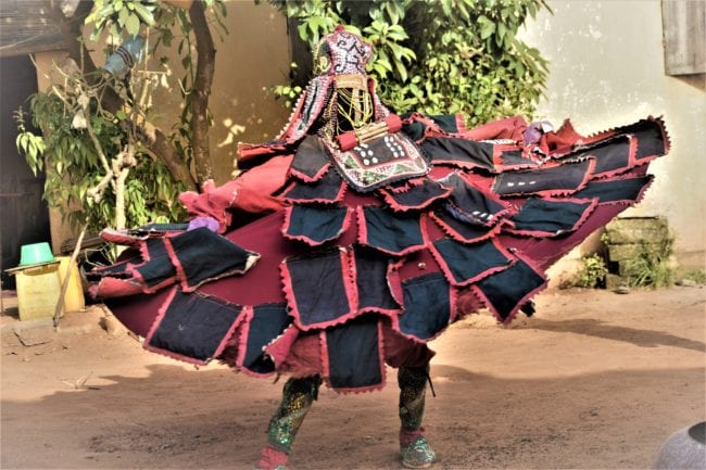 A voodoo dancer with wide billowing patch skirts in Ouidah Benin
