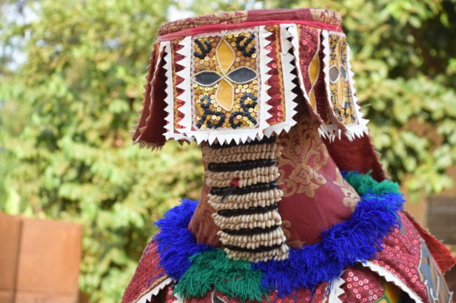 An elaborately masked Voodoo dancer at a New Year fortune telling ceremony in Benin