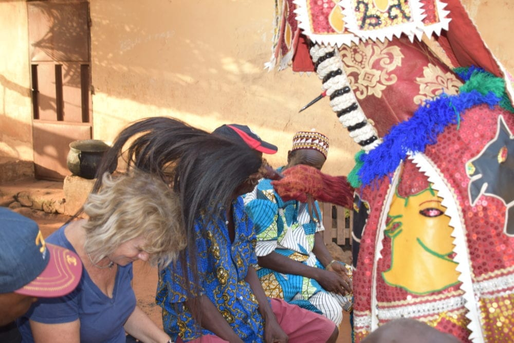 Sue being blessed by an elaborately masked Voodoo fortune teller in Benin
