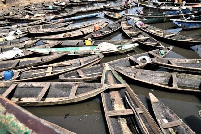 Open wooden boats, poles resting on top, wedged together on the water at Ganvie