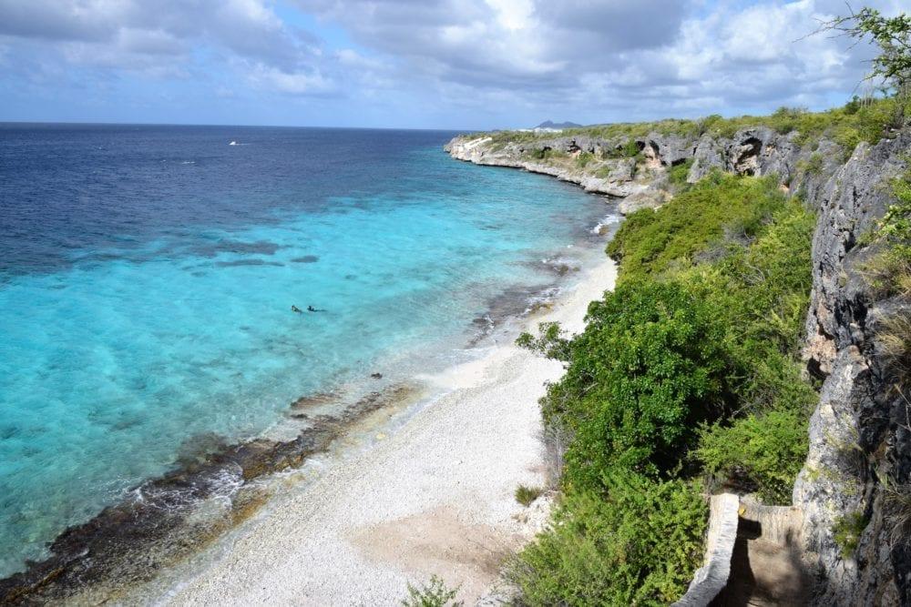 Rocky cliffs above a strip of beach and a cyan sea