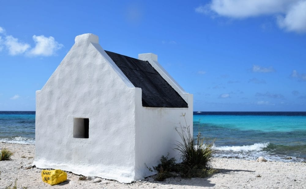 A whitewashed slave hut by the sea