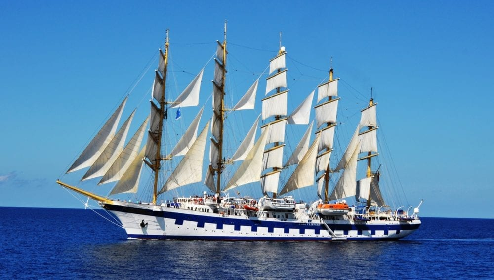 The Star Clipper in full sail against a blue sky and sea