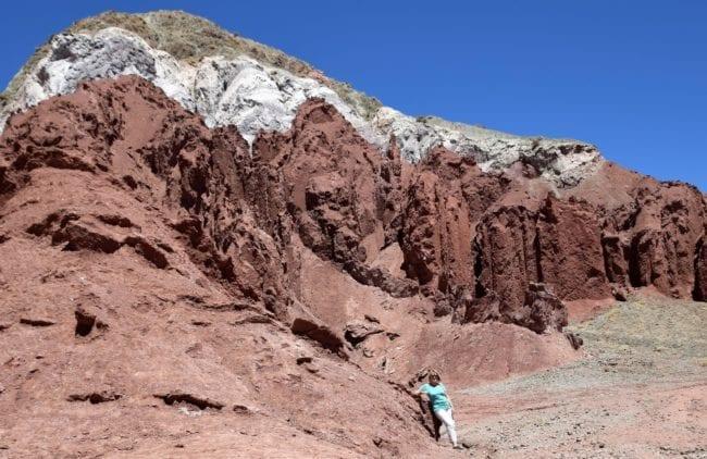 Sue below the towering striped peaks of Rainbow Valley, Atacama