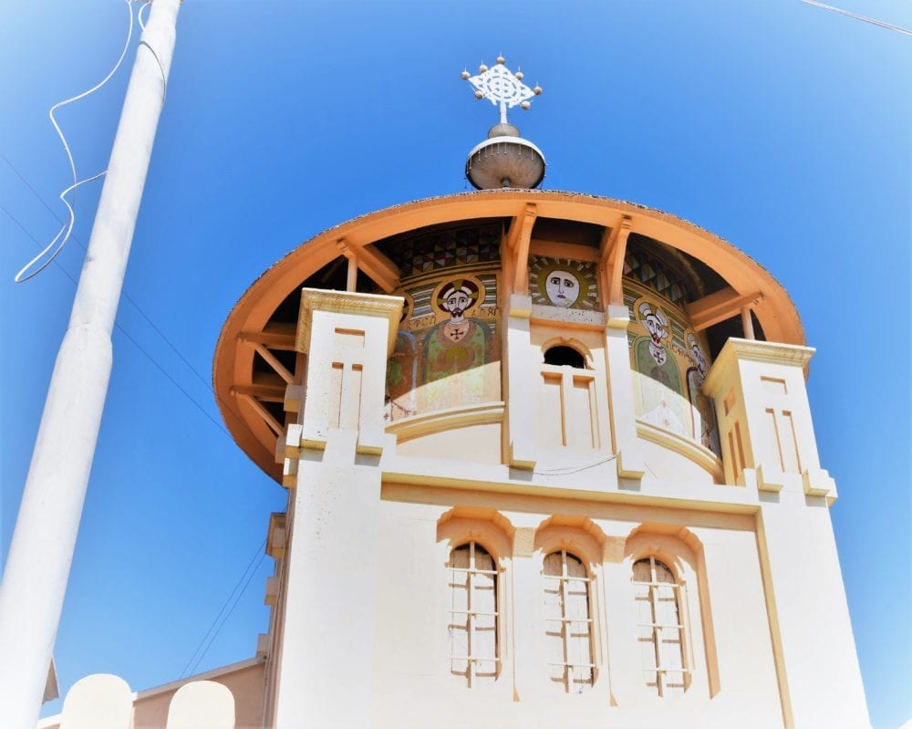 A richly decorated circular church tower framed by a blue sky in Eritrea
