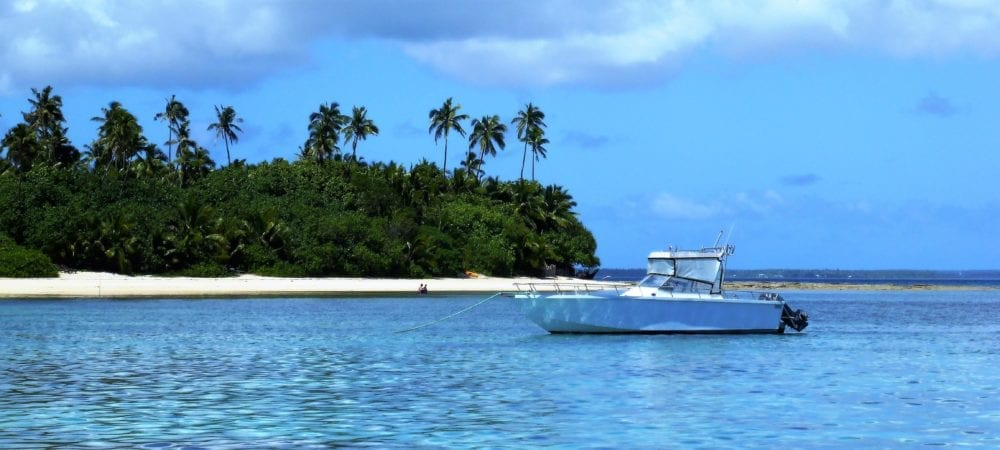 A motor boat moored off a palm tree covered islet in Tonga
