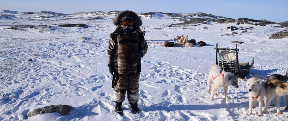 Sue wrapped up in sealskin next to the huskies and the sled. Greenland