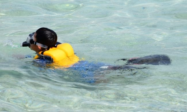 A tourist swimming in Tumon Bay wearing mask and flippers