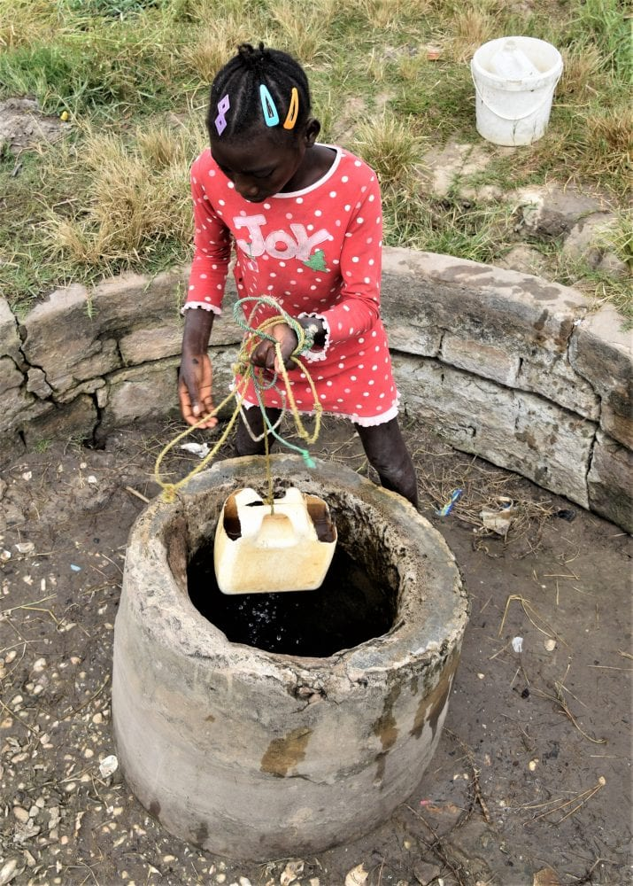 A small girl draws water from well at Holia, Guinea-Bissau
