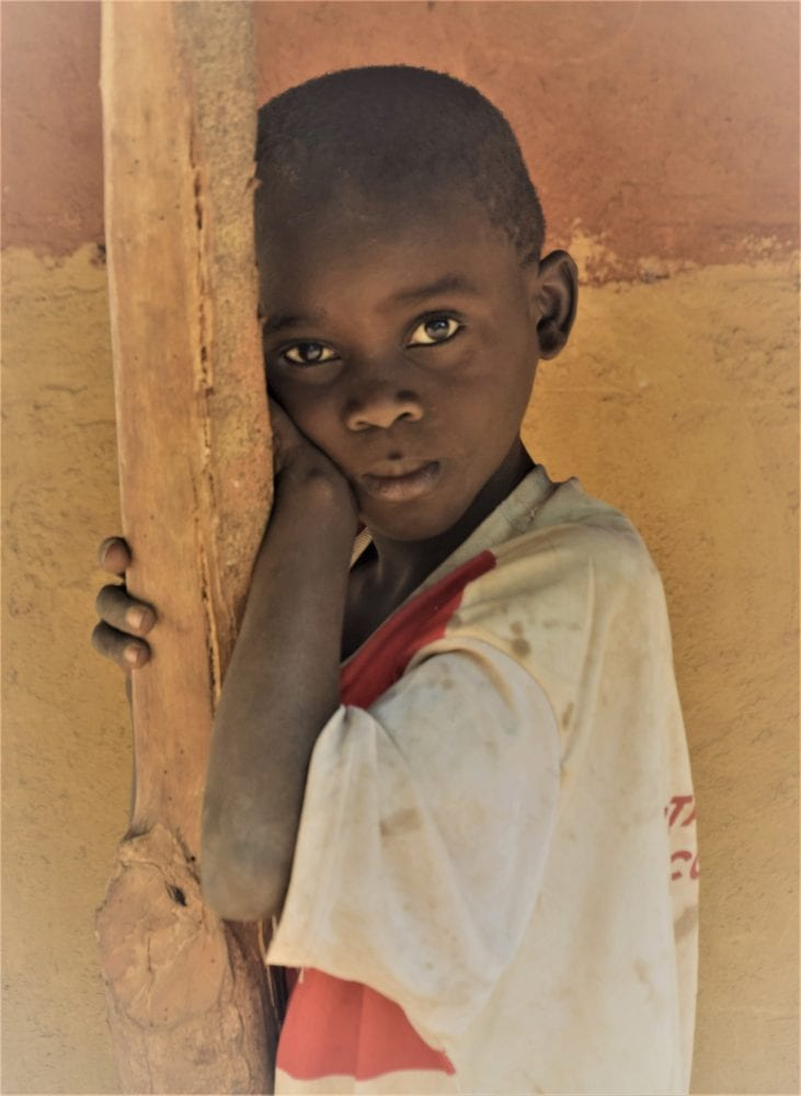 A small boy leads on a post in a hut in Guinea-Bissau