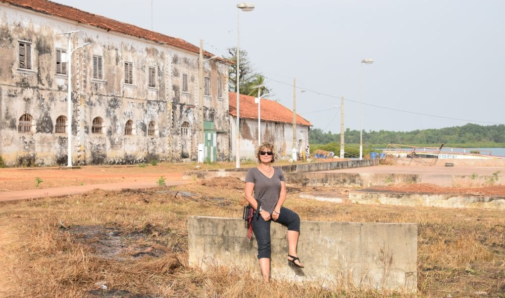 Sue in front of ruined factory buildings in Bolama