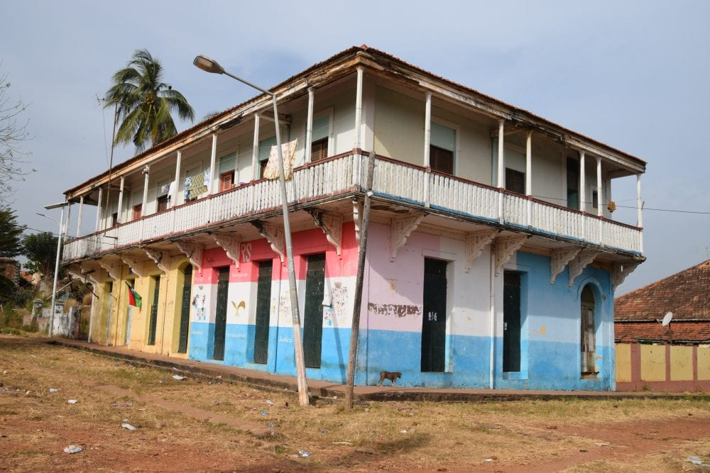 A brightly painted balconied building in Bolama