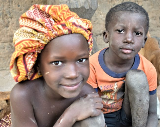 A portrait of two children in Guinea-Bissau. The girl wears a bright orange cloth hat