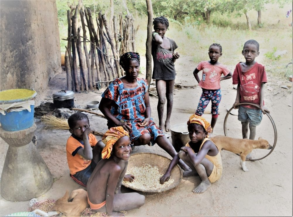 A family pose with a bowl of seeds outside their home in Guinea-Bissau