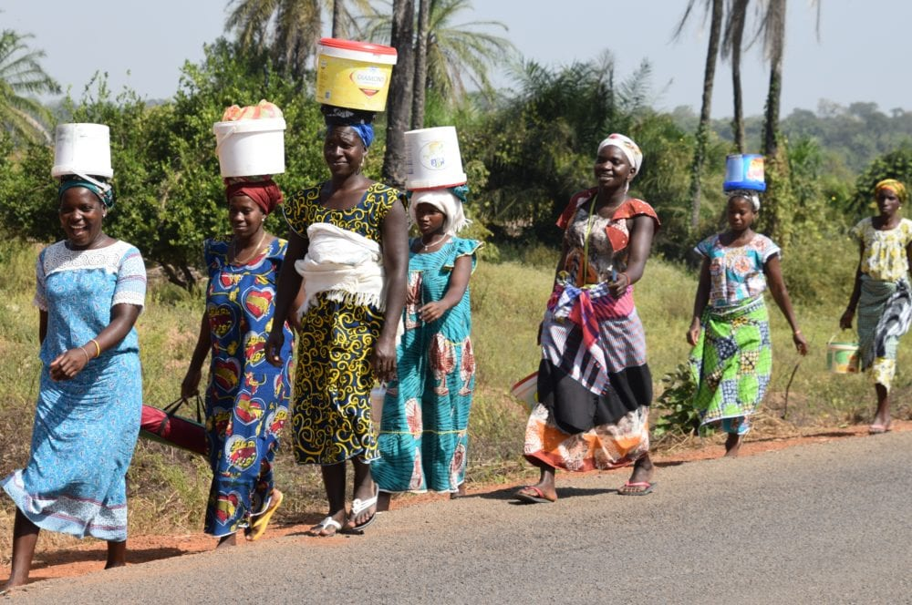 A line of ladies in bright dresses balancing tubs on their heads in Guinea-Bissau