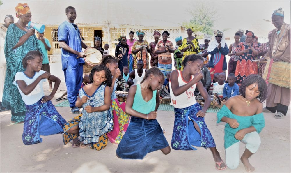 Girls dancing to the griot music, instrumentalists behind