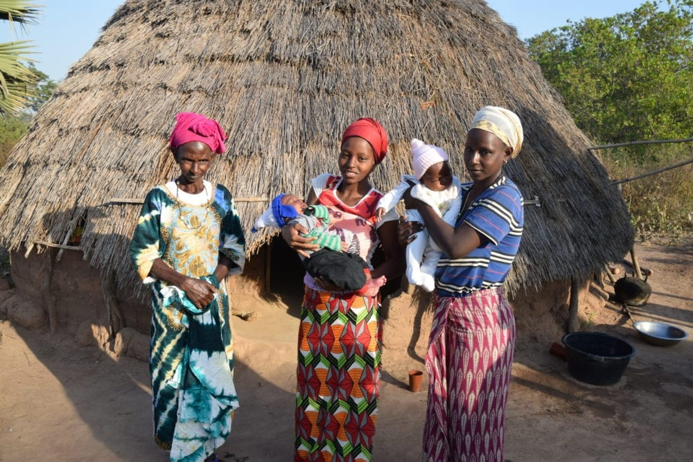 Two mothers hold up their babies outside their hut in Guinea=Bissau. Grandmother stands alongside in her best clothes