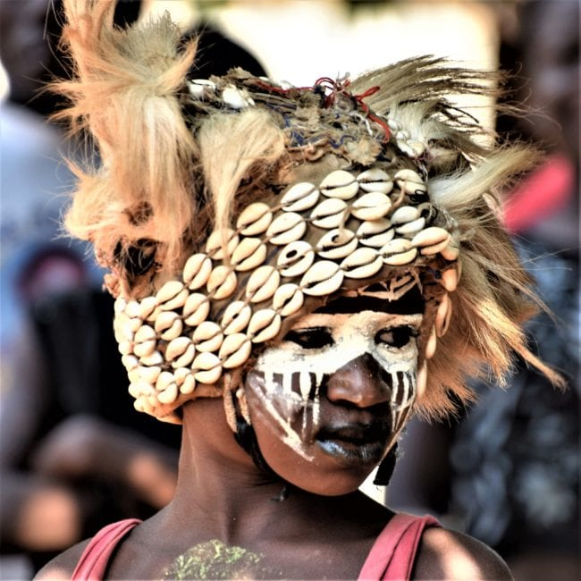 A portrait of a We people gymnastic dancer in face paint and shell headdresses,
