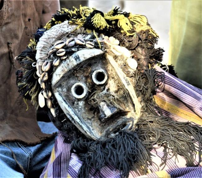 A portrait of a mask wearing dancer near Man
