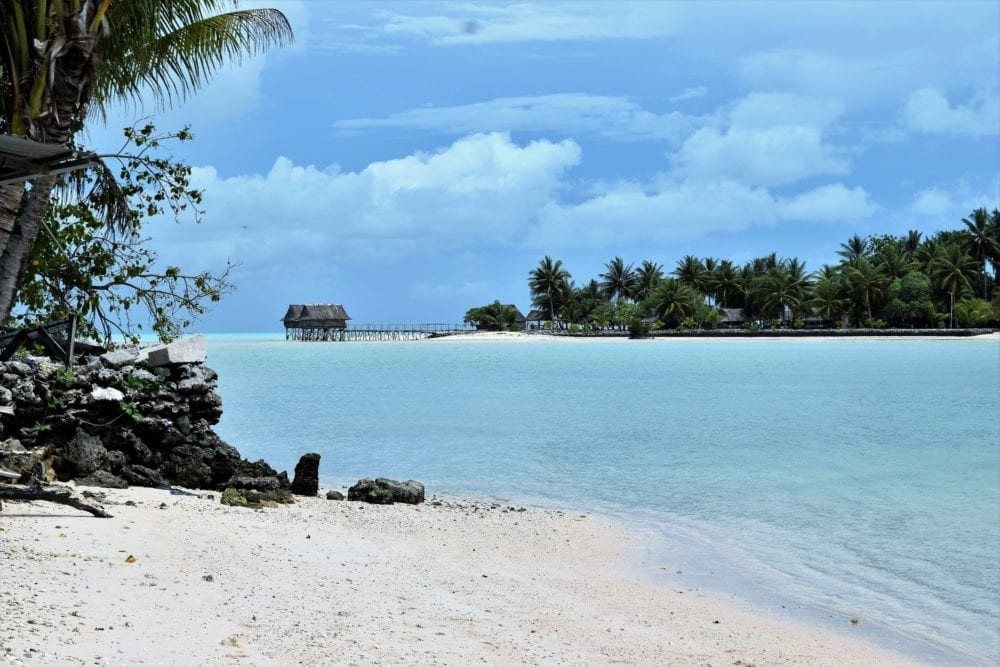A stilt house over the water at the end of a beautiful blue sea inlet in the lagoon