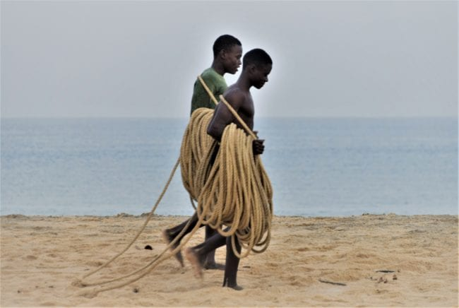 Fishermen carrying coiled ropes on the beach
