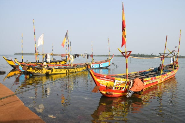 Brightly painted fishing boats reflected in the water